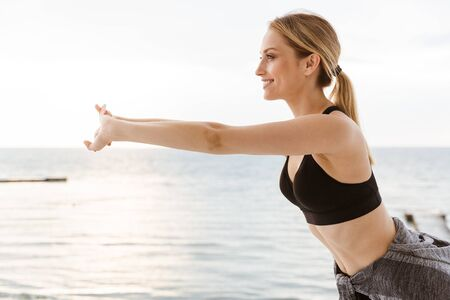 Image of blonde young woman wearing tracksuit doing exercise while working out on pier near seaside in morning Фото со стока