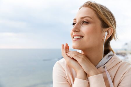 Image of nice woman wearing tracksuit smiling and listening to music with earphones while sitting near seaside in morning