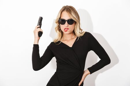 Portrait of an attractive blonde woman dressed in black dress and sunglasses standing isolated over white background, holding a gun