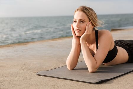 Image of young relaxed woman wearing tracksuit resting and lying on mat while working out on pier near seaside in morning 写真素材
