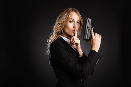 Portrait of a beautiful confident blonde haired business woman dressed in formal clothes standing isolated over black background, showing silence gesture, holding a gun 写真素材