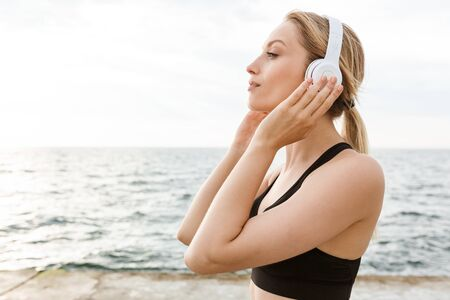 Image of calm beautiful woman wearing tracksuit listening to music with headphones near seaside in morning