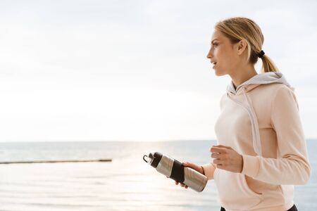 Image of blonde woman wearing tracksuit holding water bottle while working out on pier near seaside in morning