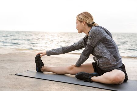 Image of caucasian focused woman wearing tracksuit doing exercise on mat while working out on pier near seaside in morning Фото со стока