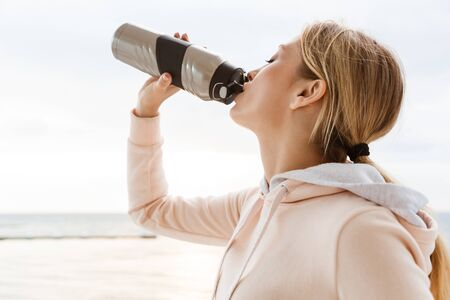 Image of young woman wearing tracksuit drinking water from bottle while working out on pier near seaside in morning Фото со стока