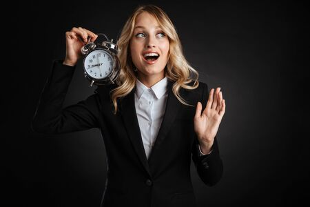 Portrait of a beautiful cheerful blonde haired business woman dressed in formal clothes standing isolated over black background, showing alarm clock, looking away Banque d'images - 130066846