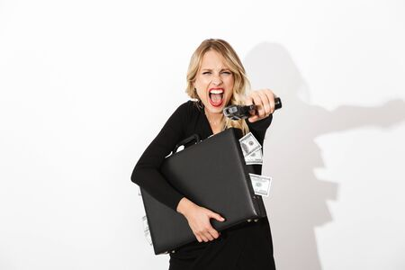 Portrait of an attractive blonde woman dressed in black dress standing isolated over white background, holding a gun, shooting while holding briefcase full of money banknotes