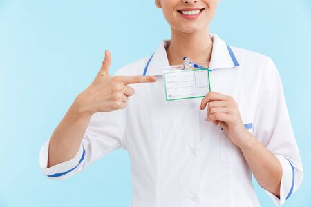 Cropped image of a beautiful smiling blonde woman doctor wearing uniform standing isolated over blue background, showing her name on badge