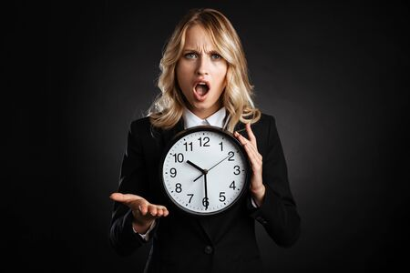 Portrait of a beautiful shocked blonde haired business woman dressed in formal clothes standing isolated over black background, showing alarm clock Banque d'images - 130066862