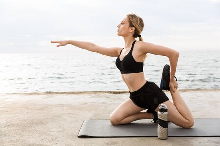 Image of seductive woman wearing tracksuit doing exercise on mat with water bottle while working out near seaside in morning
