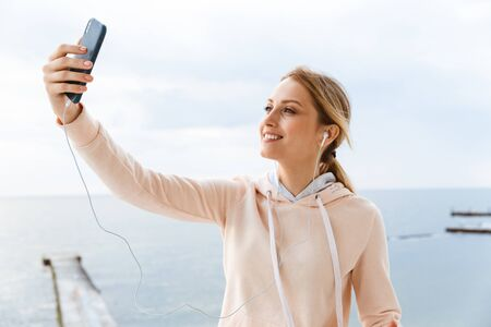 Image of happy woman wearing tracksuit listening to music with earphones and taking selfie photo on cellphone near seaside in morning