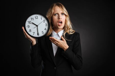 Portrait of a beautiful shocked blonde haired business woman dressed in formal clothes standing isolated over black background, showing alarm clock Banque d'images - 130066870