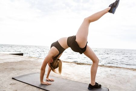 Image of caucasian sporty woman wearing tracksuit doing exercise on mat while working out on pier near seaside in morning