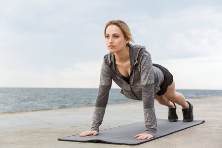 Image of blonde concentrated woman wearing tracksuit doing exercise on mat while working out on pier near seaside in morning
