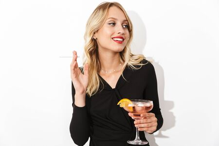 Portrait of an attractive lovely blonde woman dressed in black dress standing isolated over white background, holding a cocktail, smoking a cigarette Banco de Imagens - 130066879