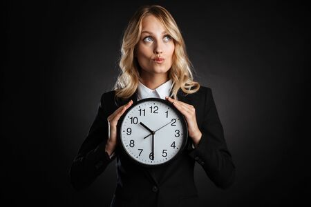 Portrait of a beautiful blonde haired business woman dressed in formal clothes standing isolated over black background, showing alarm clock, looking away Banque d'images - 130066927