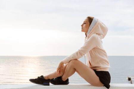 Image of calm woman wearing hoodie looking aside while sitting on pier near seaside in morning 写真素材