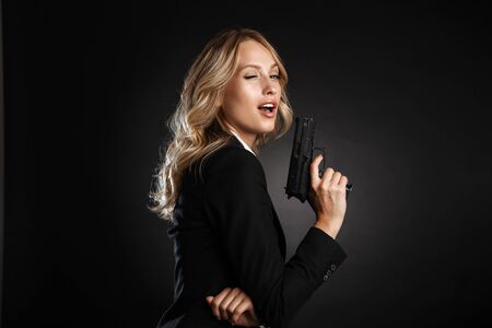 Portrait of a beautiful confident blonde haired business woman dressed in formal clothes standing isolated over black background, winking, shooting with a gun