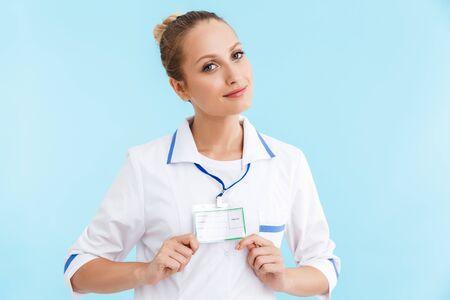 Belle femme blonde souriante médecin en uniforme debout isolé sur fond bleu, montrant son nom sur l'insigne
