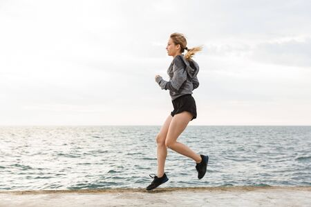 Image of blonde sporty woman wearing tracksuit jumping while working out on pier near seaside in morning