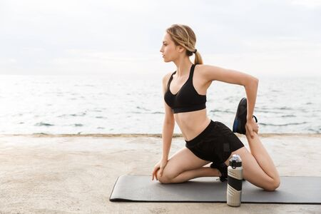 Image of serious woman wearing tracksuit doing exercise on mat with water bottle while working out near seaside in morning