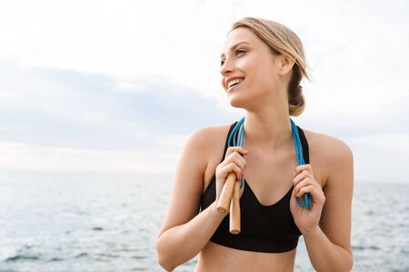 Image of cheerful woman wearing tracksuit smiling with jumping rope over neck while working out near seaside in morning