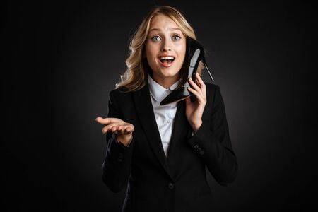 Portrait of a beautiful blonde haired business woman dressed in formal clothes standing isolated over black background, pretend talking on mobile phone, holding high heel shoe