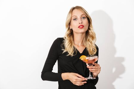 Portrait of an attractive lovely blonde woman dressed in black dress standing isolated over white background, holding a cocktail Banco de Imagens - 130066963