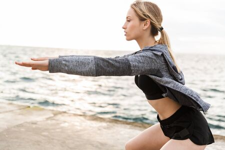 Image of caucasian woman wearing tracksuit doing exercise with eyes closed while working out on pier near seaside in morning Фото со стока