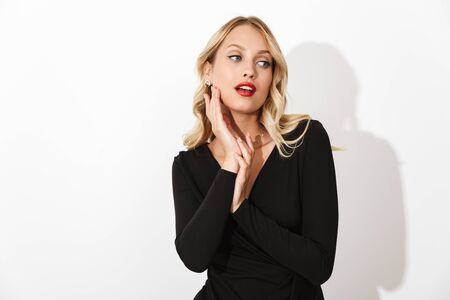 Portrait of an attractive blonde woman dressed in black dress standing isolated over white background, posing Banco de Imagens - 130066985