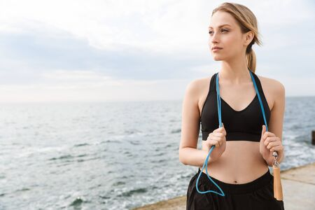 Image of attractive woman wearing tracksuit standing with jumping rope over neck while working out near seaside in morning