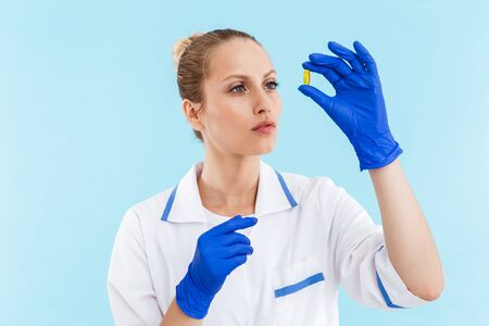 Beautiful confident blonde woman doctor wearing uniform standing isolated over blue background, looking at a pill 写真素材