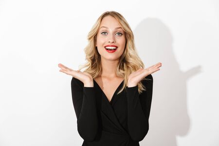 Portrait of an attractive blonde woman dressed in black dress standing isolated over white background, posing Banco de Imagens