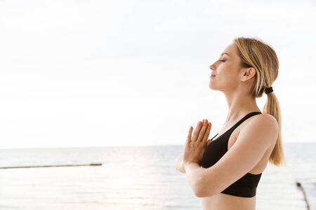 Image of blonde nice woman wearing tracksuit keeping palms together while meditating on pier near seaside in morning