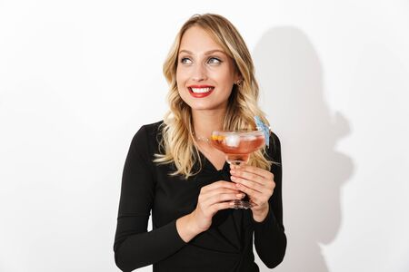 Portrait of an attractive lovely blonde woman dressed in black dress standing isolated over white background, holding a cocktail Banco de Imagens - 130067078