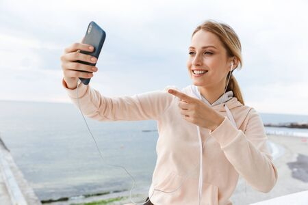 Image of smiling woman wearing tracksuit listening using earphones and pointing finger at cellphone near seaside in morning