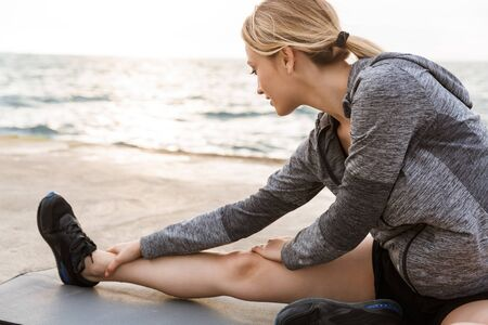 Image of caucasian strong woman wearing tracksuit doing exercise on mat while working out on pier near seaside in morning