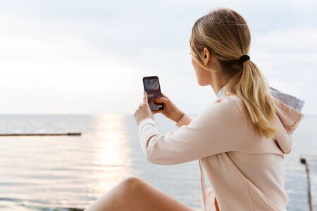 Image of blonde woman wearing tracksuit taking photo on cellphone while sitting on pier near seaside in morning