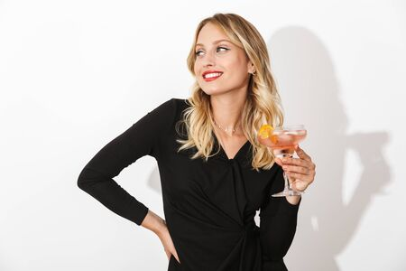 Portrait of an attractive lovely blonde woman dressed in black dress standing isolated over white background, holding a cocktail Banco de Imagens - 130067083