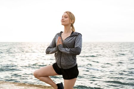 Image of blonde relaxed woman wearing tracksuit meditating and doing exercise while working out on pier near seaside in morning 写真素材