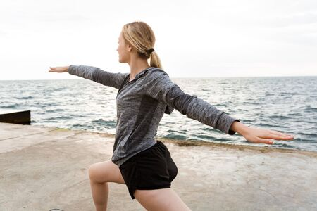 Image of caucasian sporty woman wearing tracksuit doing exercise while working out on pier near seaside in morning