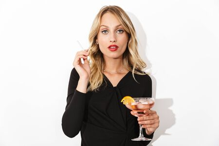 Portrait of an attractive blonde woman dressed in black dress standing isolated over white background, holding a cocktail