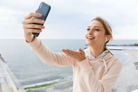 Image of smiling woman wearing tracksuit holding copy space while taking selfie photo on cellphone near seaside in morning