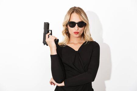 Portrait d'une jolie femme blonde vêtue d'une robe noire et de lunettes de soleil isolées sur fond blanc, tenant une arme à feu