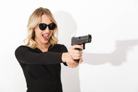 Portrait of an attractive blonde woman dressed in black dress standing isolated over white background, holding a gun, screaming