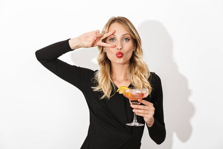 Portrait of an attractive lovely blonde woman dressed in black dress standing isolated over white background, holding a cocktail Banco de Imagens