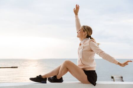 Image of caucasian woman wearing tracksuit smiling and throwing up arms while sitting near seaside in morning