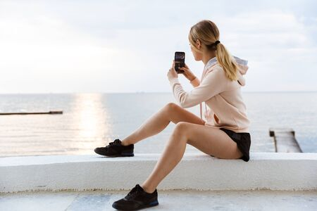 Image of young woman wearing tracksuit taking photo on cellphone while sitting on pier near seaside in morning
