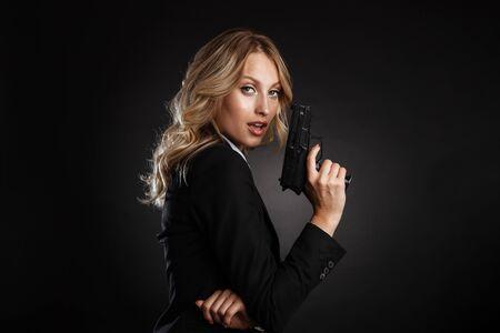 Porträt einer schönen blonden Geschäftsfrau in formeller Kleidung, die isoliert auf schwarzem Hintergrund steht und mit einer Pistole schießt