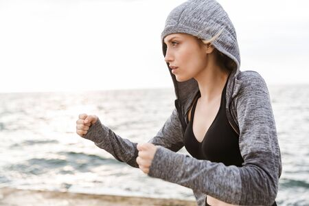 Image of serious blonde woman wearing hoodie boxing while working out on pier near seaside in morning Stock Photo